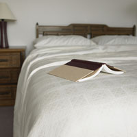 Open book on corner of double bed
