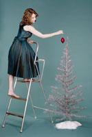Woman putting Xmas decoration on tree 11034001170| 写真素材・ストックフォト・画像・イラスト素材|アマナイメージズ