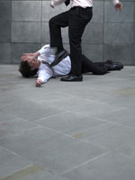 man kicking younger colleague lying
