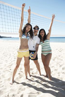 woman and two girls cheering on beach