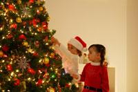 クリスマスツリーの飾り付けをする子供2人