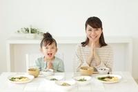 和朝食を食べる女の子とお母さん