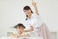 勉強する女の子と指差す先生
