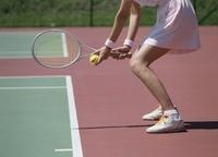 テニスボールを握りラケットを構える女性