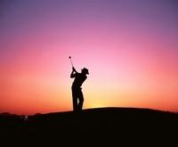 夕陽の中のゴルファーのシルエット