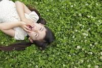 緑のクローバーの上で寝転がる女の子