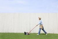 芝生の庭の芝刈りをする男性