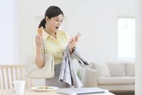 出勤前にスマートフォンを見ながら朝食を食べる女性 11038022062| 写真素材・ストックフォト・画像・イラスト素材|アマナイメージズ