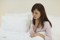 体調不良で喉を押さえる女性 11038022252| 写真素材・ストックフォト・画像・イラスト素材|アマナイメージズ
