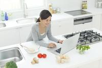 キッチンでパソコンを見てメニューを検索する女性