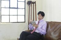 ソファーで寛ぎながら仕事をするビジネスマン