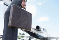 Businesswoman Holding a Briefcase outside of airplane  low