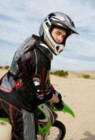 Motocross Racer on bike in desert  (portrait)
