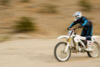 Motocross racer travelling at speed  outdoors 11044002405| 写真素材・ストックフォト・画像・イラスト素材|アマナイメージズ