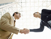Businessman and businesswoman shaking hands  (low angle vi