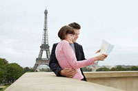 France  Paris  Couple reading map on balcony in front of E
