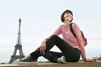 France  Paris  Young woman sitting on balcony in front of
