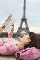 France  Paris  Young woman reading book on balcony with Ei 11044005527| 写真素材・ストックフォト・画像・イラスト素材|アマナイメージズ