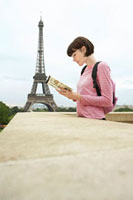 France  Paris  Young woman reading book on balcony in fron