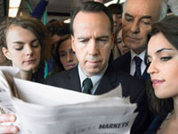 Commuters standing on train  reading newspaper over should