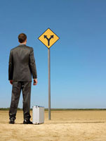 Businessman standing by briefcase  looking at road sign in