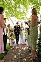 Bride and groom walking on path  people throwing flower pe