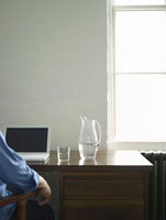 Person sitting at desk with laptop and jug of water  back