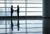 Silhouettes of two business men shaking hands