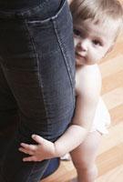 Todller holds onto mothers legs  first steps 11044012055| 写真素材・ストックフォト・画像・イラスト素材|アマナイメージズ