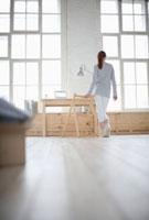 Woman walks across loft apartment 11044012102| 写真素材・ストックフォト・画像・イラスト素材|アマナイメージズ