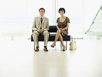 Businesspeople Sitting on Bench in airport