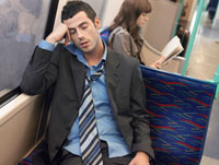Businessman with loosened tie  sleeping on Commuter Train