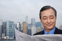 Middle-aged business man reading newspaper office buildings