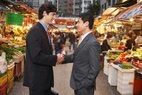 Two business men shaking hands at street market 11044017180| 写真素材・ストックフォト・画像・イラスト素材|アマナイメージズ