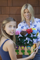 Portrait of a little girl handing over artificial flowers in