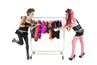 Punk women pulling dress in front of clothes rack over white