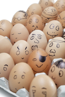 Various facial expressions painted on brown eggs arranged in