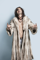 Portrait of young man in fur coat gesturing rock music sign