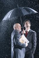 Businessmen Watching Rain from Under Umbrella