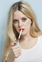 Portrait of young blond woman igniting cigarette against lig