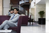 Business man sitting on sofa using cell phone