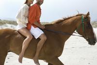 Mid-adult couple riding horse on beach 11044021876| 写真素材・ストックフォト・画像・イラスト素材|アマナイメージズ