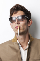 Young man in sunglasses smoking cigarette against white back