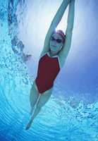 Full length of female swimmer in United States with arms rai