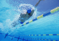 Young professional male athlete doing backstroke in swimming
