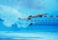 Underwater shot of three male athletes racing in swimming po