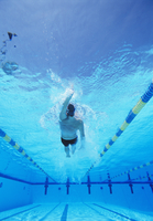 Underwater shot of young male athlete doing backstroke in sw