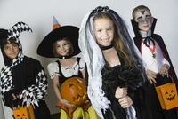 Portrait of boys and girls (7-9) wearing Halloween costumes