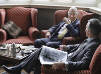 Two business men sitting in lobby talking one holding newspaper 11044027707| 写真素材・ストックフォト・画像・イラスト素材|アマナイメージズ