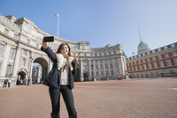 Happy woman taking self portrait against Admiralty Arch in London, England, UK
